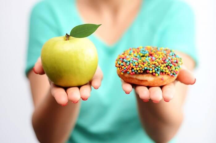 Es difícil elegir el concepto de comida saludable, con la mano de la mujer sosteniendo una manzana verde y una dona de bomba calórica