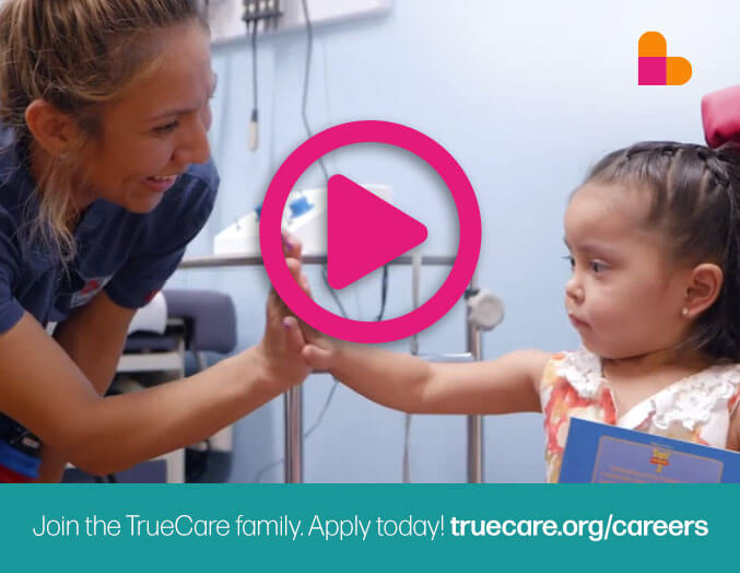 TrueCare video snapshot of a healthcare worker giving a female child a high five