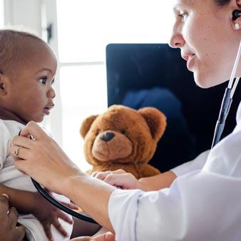 Baby visiting a TrueCare doctor for a checkup teddy bear in the background