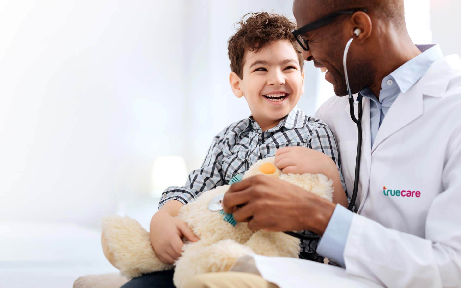 Enthusiastic male TrueCare doctor sitting with boy while listening to plush bear and talking