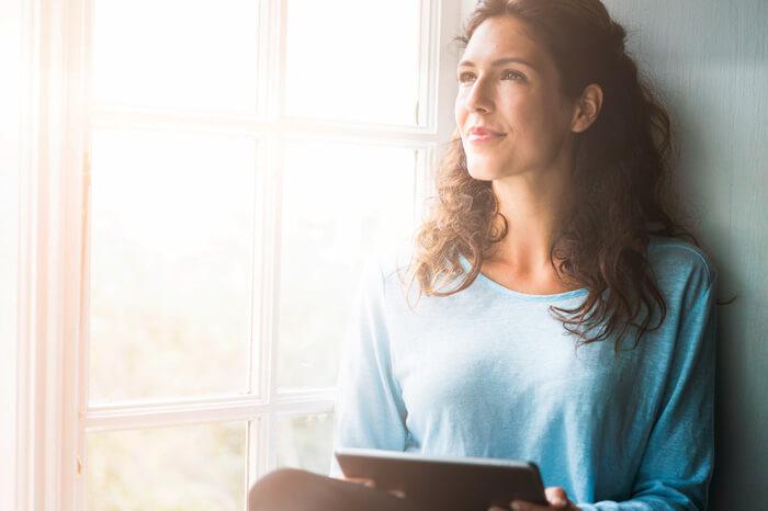 Una foto de una mujer pensativa sentada en el alféizar de la ventana. Joven hembra está sosteniendo tableta digital mientras mira hacia otro lado. Lleva ropa casual en una habitación luminosa.