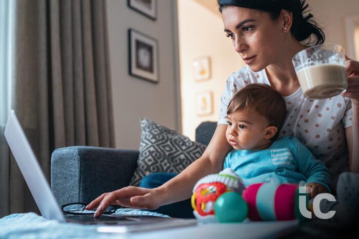 Joven madre moderna con un bebé usando portátil en casa