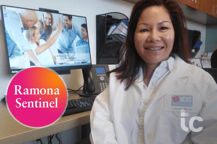 Mujer asiática Doctor sonriendo sentado frente a una pantalla de ordenador
