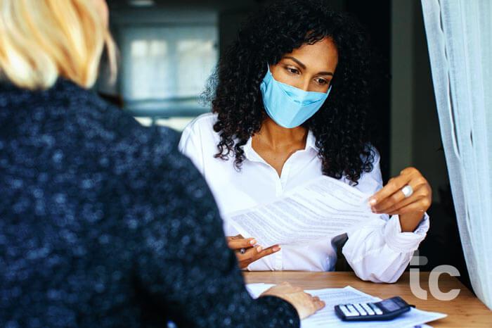 Dos mujeres mirando y leyendo un contrato en el escritorio con mascarillas